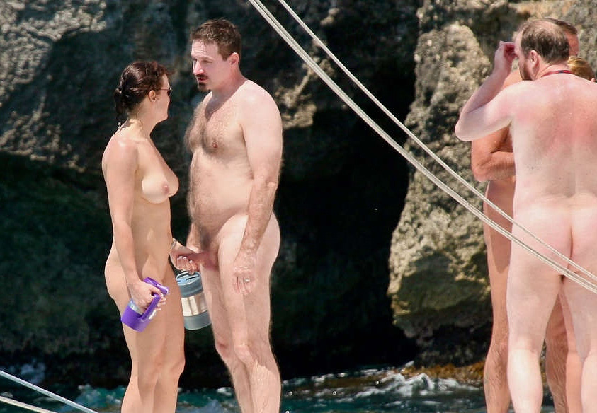 Woman Holds Naked Man S Erect Penis On A Nude Beach Other Men